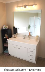 A white and stainless steel modern bathroom vanity, mirror and accessories.