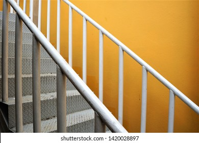 White stairs and banister outside the building near the yellow wall.