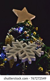 A white star on top of a Christmas tree, christmas decoration and a big artificial snowflake.