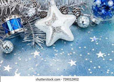 white star, silver drum and glass balls on silver fir tree branch with cones on blue glitter background