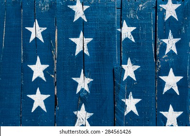 White stars on blue painted on planks of rustic reclaimed wood. Background for July 4th, Memorial Day, Veterans Day, Labor Day or other patriotic occasion.