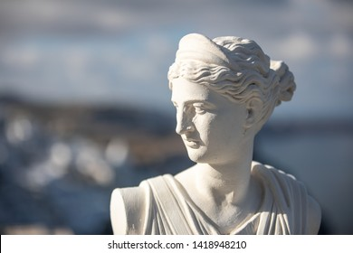 White statue of Artemis, Diana goddess with blurred Santorini Fira view in Greece. Historical portrait and traditional art in Greece