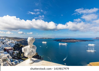 White statue and sea caldera view Santorini, Greece. Famous attraction of white village with cobbled streets, Greek Cyclades Islands, Aegean Sea. Wonderful summer urban landscape