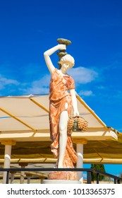 White statue woman carrying vase   fruits outside