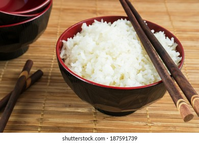 White steamed rice in a bowl with chopsticks