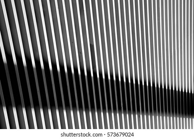 white steel battens wall with light and shadows. - monochrome