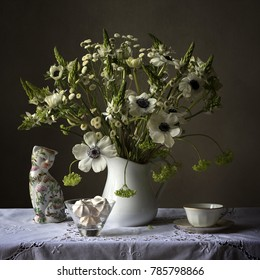 white still life anemone flower arrangement bouquet with a chinese porcelain cat, tea cup and meringues