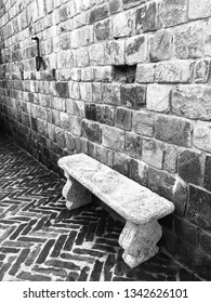 A white stone bench nestled on a zig zag brick patio against a hand hewn brick wall in black and white. There is a lot of texture and contrast between the shades and the shape of the bricks.