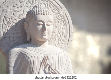 The White Stone Buddha Statue With Light Bokeh background and light from Buddha's head in BanDen temple in Chiang Mai, Thailand for background or textures and other. Close up.