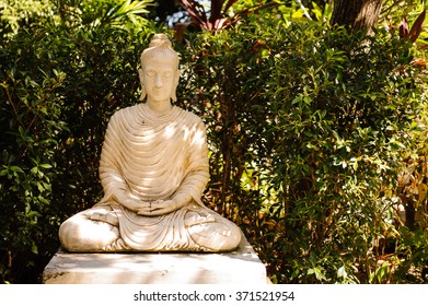 white stone Buddha statue in Thailand green background