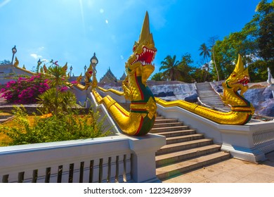 White stone Buddhist temple on a dais, the roof is decorated with carved patterns on wood, a picturesque staircase with golden dragons on the edges. Wat Kaew, Krabi Town, Thailand.