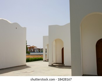 The white stone building with arches and brown doors facing each other