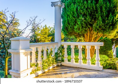 White stone fence with columns among the greenery in the park.