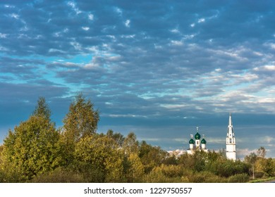 White stone Orthodox church with green domes against a cloudy sky in the early morning, Russia.