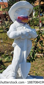 A white stone statue of a garden worker wearing a crocheted mask  and placed in a garden