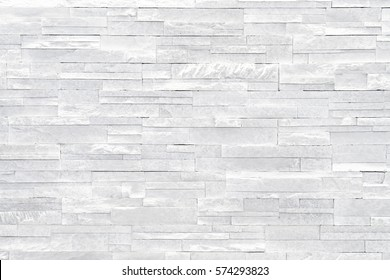 White stone wall background. Stacked stone tiles are often used in interior design decors as accent wall. Use this gray texture in graphic design to create a wallpaper, background, backdrop and more!