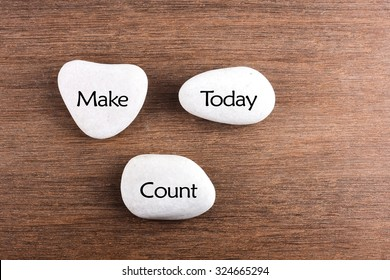 White stones with Make today count word on wooden background