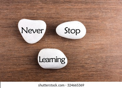 White stones with Never stop learning word on wooden background