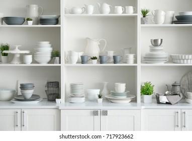 White storage stand with ceramic dishware in kitchen