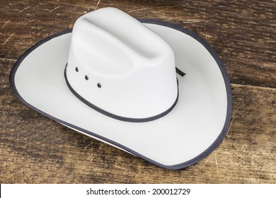 A white straw cowboy hat sitting on a wood table. e7298d413e0f