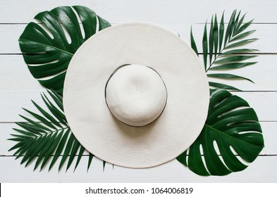 White straw hat, green plam leaves on wooden baclground. Summer holidays vacation concept. Poster banner, postcard template.