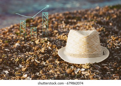 White straw hat on the sand with a business schedule at the sunrise. Concept passive income