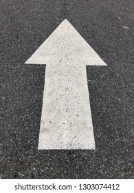 White street arrow pointing to direction of traffic.