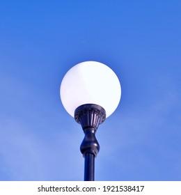 white street lamp on cast iron leg against blue sky on a sunny day
