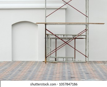 white street wall with scaffolding in city