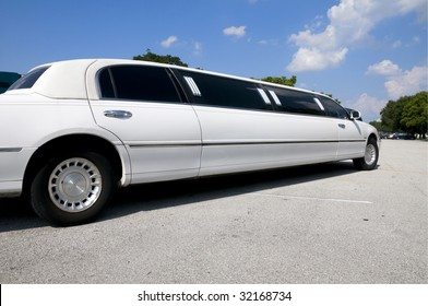 White stretch limousine with partly cloudy blue sky