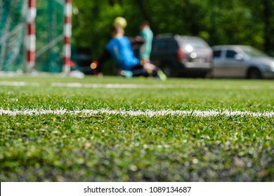 White stripe on green soccer field from side view. Artificial turf of football field