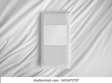 White striped fabric bed linen items in the PVC retail pack with empty label against the white sheet. Folded bed linen in the bag. Photo ready for mock up.