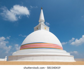 White Stupa Dagabo On Sand Wrapped With Buddhist Flag And Blue Sky Clouds At Nelligala
