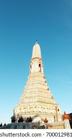 The white stupa of temple of dawn with blue sky and sun light, Thailand