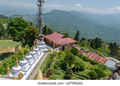White stupa in Zang Dhok Palri Phodang  a Buddhist monastery in Kalimpong in West Bengal, India. and blue sky with clouds in the background .