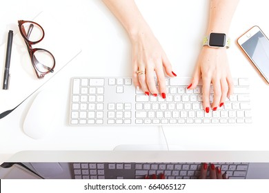 White style top view, computer workspace and female hands.