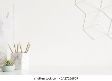 White and stylish home interior with cool office accessories, notebooks, marble box   geometric organizer and air plants. Scandinavian home decor. Minimalistic concept. Template. Copy space.