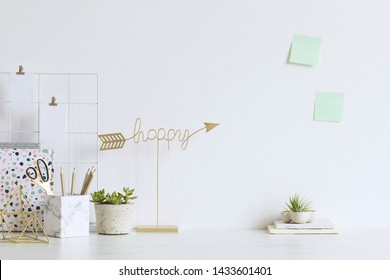 White and stylish home interior with cool office accessories, notes, boxes, pencils and air plant. Gold happy sign. Scandinavian home decor. Minimalistic concept. Template. Copy space. White walls.