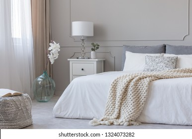 White stylish lamp on wooden nightstand next to flower in big glass vase in contemporary bedroom interior