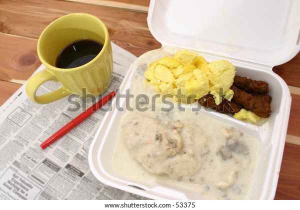 White styrofoam box of breakfast (sausage, eggs, biscuits, gravy) and a yellow mug of coffee sitting on a newspaper.  Newspaper blurred to hide names and phone numbers.