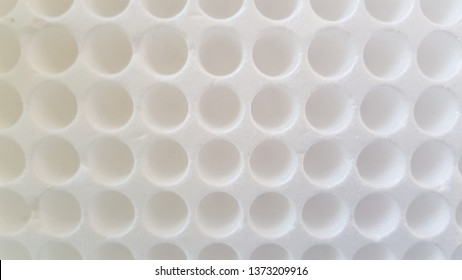 White styrofoam packaging box with round holes for medical test tubes. Abstract background with circled pattern. White geometric shaped backdrop.