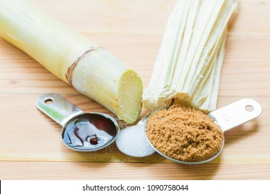 White sugar,  brown sugar, molasses, bagasse  and cane on wooden background. There are by product of sugarcane.