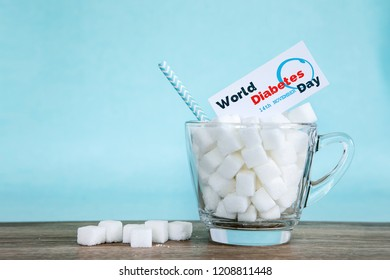 White sugar cube in glass on wooden table with light blue background , unhealthy sweet food concept for 14th November campaign of World Diabetes Day