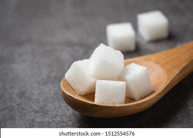 white Sugar cube in wood spoon on table.