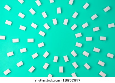White sugar cubes arranged on turquoise background, top view