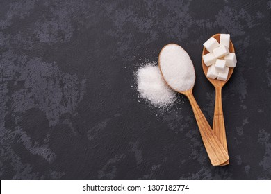 White sugar cubes  and granulated sugar  in two spoons with white sugar on  black table.Top view