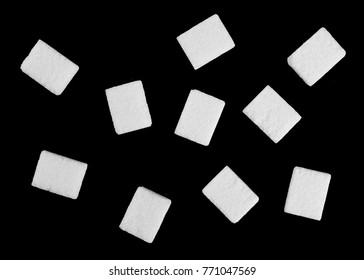 White sugar cubes isolated on black background and texture