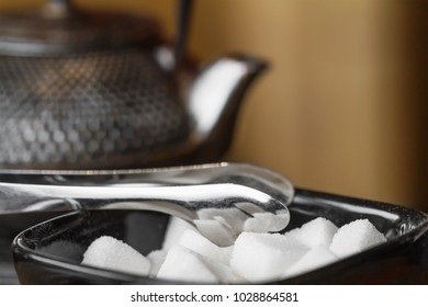 White sugar cubes on the black plate with sugar tongs. Metal vintage asian teapot on the background. Closeup, selective focus