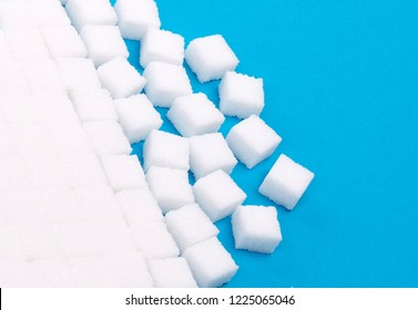 White sugar cubes on a blue solid background