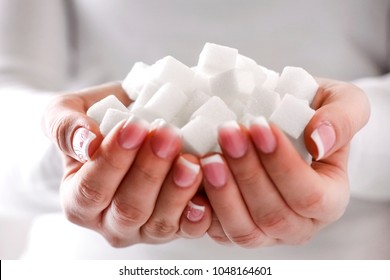 White sugar cubes in woman beautiful hands and perfect nails. Heap of white sugar.